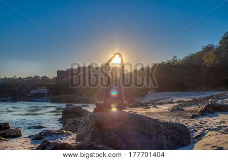 Yoga man sitting on the Ganga river bank on a big stone and meditatting on the beach near Rishikesh Uttharakand India