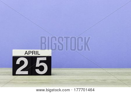 April 25th. Day 25 of month, calendar on wooden table and purple background. Spring time, empty space for text.