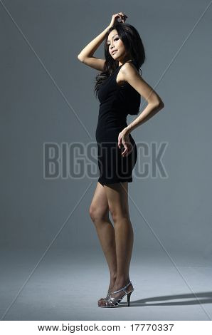 Portrait of cute female fashion model posing on light background
