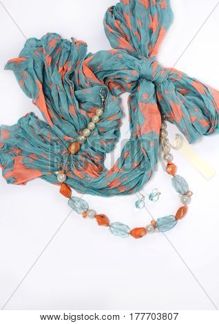 Necklace and earrings of natural stones on a white background closeup with blue scarf
