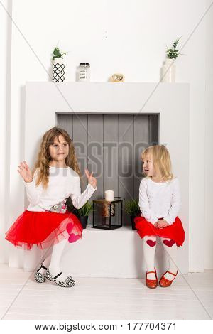 two girls in red skirts sit in front of a decorative fireplace
