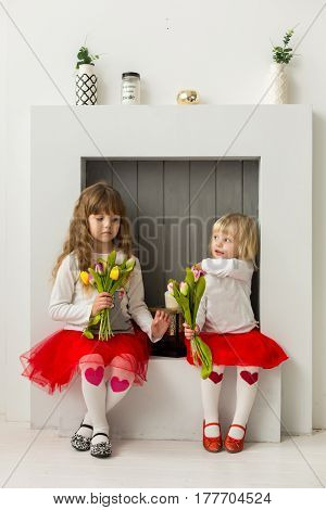 two girls in red skirts sit in front of a decorative fireplace. Holding lulani.