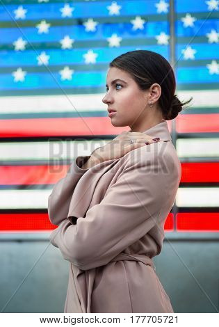 Beautiful woman standing in front of american flag and looking to the side. People nation patriotism concept.