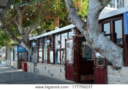 TIBERIAS ISRAEL - FEBRUARY 26 2017: Restaurant on the Tiberias waterfront. Trunks of trees grow through the wall of the restaurant
