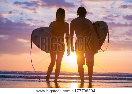 Couple of surfers standing on the beach with boards