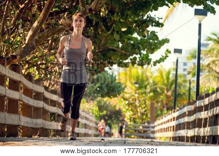 Slim young woman running on the wooden walkway in the park