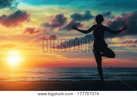 Sunset yoga woman on Ocean coast.