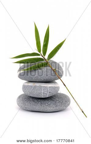 Stacked of stones with bamboo leaf on white background