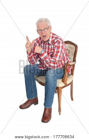 Handsome senior citizen sitting in an armchair has an unexpected good idea isolated for white background.