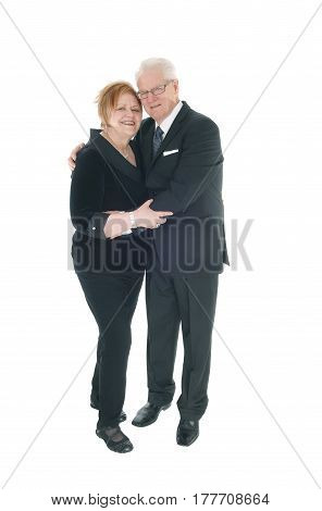 A lovely older couple standing in suits hugging each other in full lengths isolated for white background.