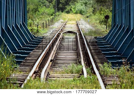 Old abandoned blue metal railroad bridge with tracks