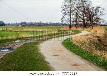 Winding dirt road in a rural landscape in the Netherlands on a cloudy day in the beginning of the spring season.