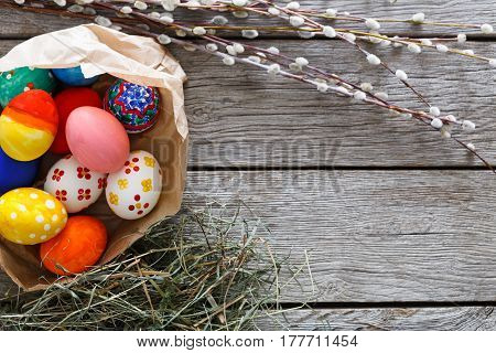 Handmade easter diy painted eggs in craft paper nest on wood background. Colorful holiday decoration on rustic table top view with copy space