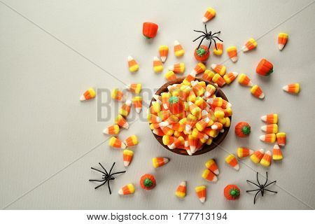 Bowl with colorful Halloween candies on light background
