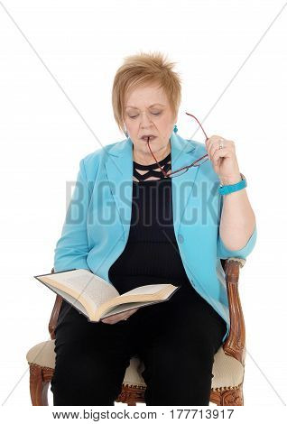 A lovely senior citizen woman in a blue jacket sitting in an old armchair reading a book with her glasses in mouth isolated for white background.