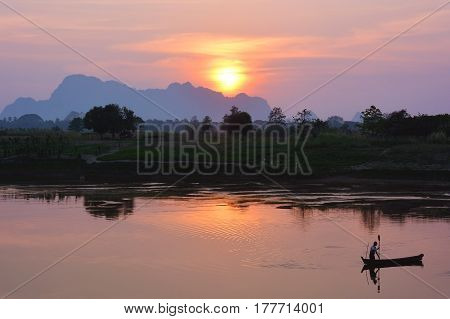 Silhouette of asian fisherman floating in the boat at the sunset in Hpa-An Myanmar