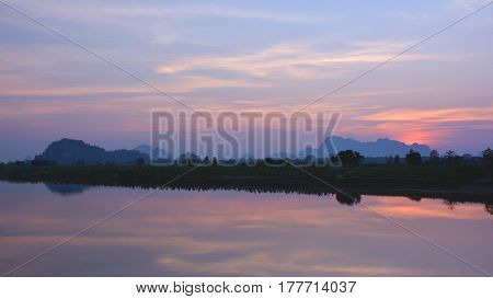Beautiful tropical sunset over the Salween river with mountains on the background Myanmar