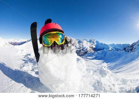 Picture of funny snowman wearing safety helmet, ski mask and gloves against beautiful mountain scene