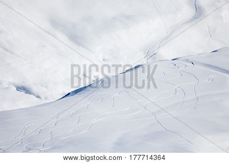 Top view picture of snowy mountains hill cowered with curving ski or snowboarding traces