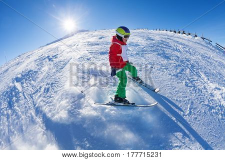 Portrait of kid boy in safety helmet and mask speeding on the ski route at sunny day