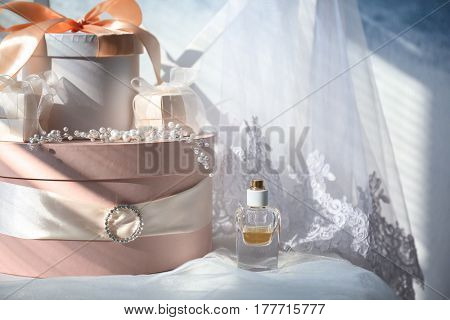Gift boxes, perfume and bridal veil on white chair