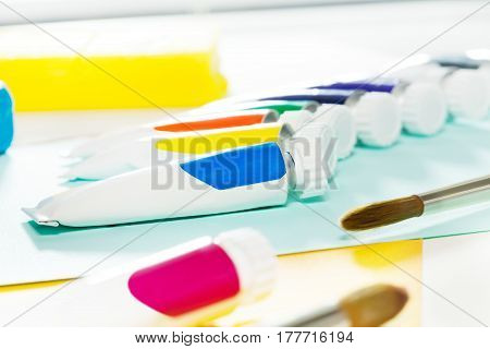 Set of blanked tubes with multicolored oil paint and brushes laying on the table