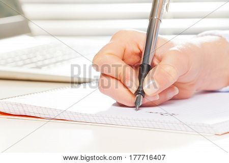 Female hand with metallic fountain pen writing on notebook at the desk