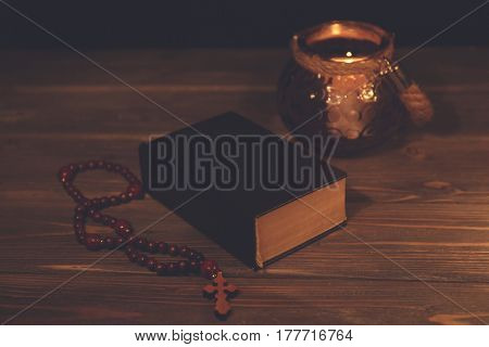 Bible with rosary on wooden table