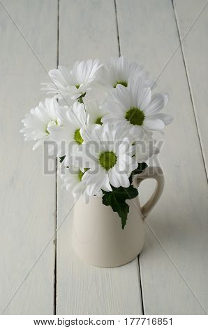 A small bunch of white flowers (Chrysanthemums) with green leaf in a beige jug on creamy off-white painted wood planks.