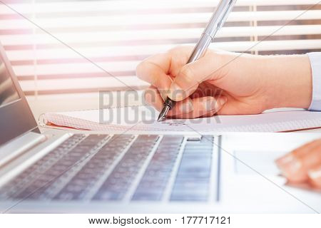 Close-up picture of woman's hands using laptop and making notes on notepad with metallic fountain pen