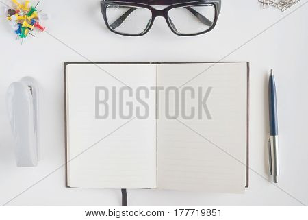 Office stationery such us glasses, pen, stapler, paper clip and notebook for writing text