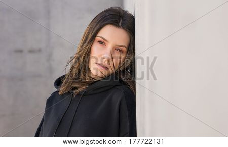 Young woman leaning against wall, contrasting grey wall background