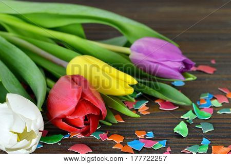 Easter card with colorful Easter flowers and colored eggshell on wooden background