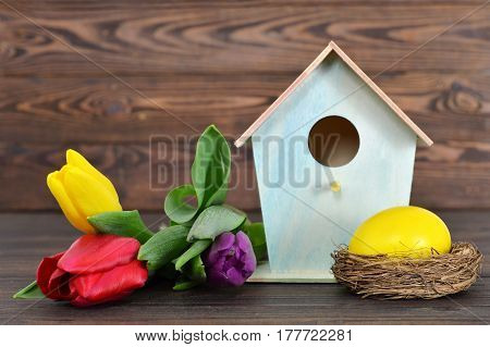 Easter card with Easter egg in the nest birdhouse and spring flowers
