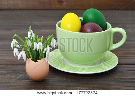 Easter eggs in the cup and spring flowers in eggshell