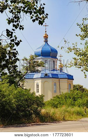 The reflection of the sun in the dome of the Rural Christian Church in Ukraine. Landscape with Church on the side of the road with trees and shrubs