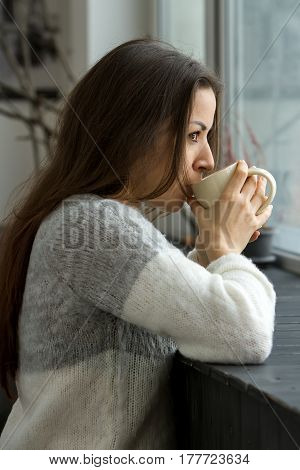 A girl in a light sweater looks out into the distance through the window drinking from a beige cup leaning on a wooden window sill.