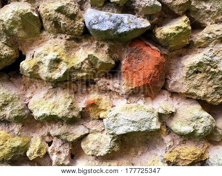 Uneven textured stone wall background with different sizes and shapes of stones and colors including blue and orange.
