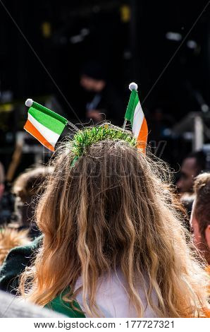 People celebrating St. Patrick day in Trafalgar Square while on stage performing Irish music groups