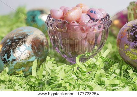 Easter Eggs and Jelly Beans in a glass container and on green crepe paper