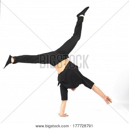 Young muscular breakdancer man stands on his hand. He is wearing black clothes on white background