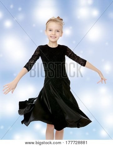 The slender little blonde girl dancer in the long dress of black color made specifically for performing .The girl gracefully spinning , the edges of her dress fluttering in the wind.Blue Christmas festive.