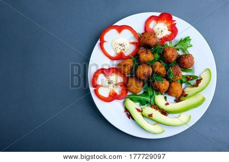 Vegetarian falafels and vegetables on a plate . With pepper and herbs and avocado. Closeup.