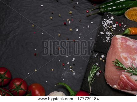Raw Pork Meat On A Cutting Board With Rosemary, Vegetables And Spices.
