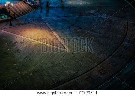 Street lamp light in the night cast rays on the street. Vivid lowlight image.