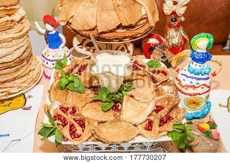 Pancakes with condensed milk and decorated with pomegranate seeds and leaves of fragrant mint during the celebration Russian Shrovetide (pancake week)