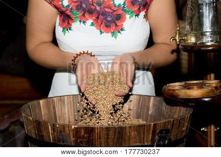 The girl's hand pours a handful of wheat grain in a wooden barrel