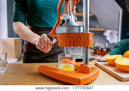 Beautifulgirl in green shirt making detox juice from orange with juicer. In the kitchen in the restaurant