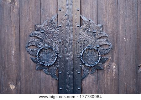 Wooden brown door of planks with metal handles and keyhole