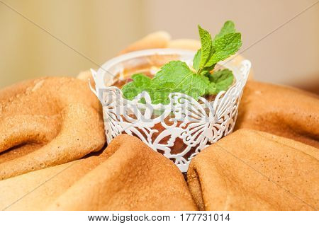 Beautifully stacked pancakes, a bowl of jam, decorated with leaves of fragrant mint during the celebration Russian Shrovetide (pancake week)